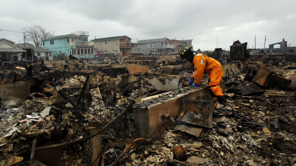 A firefighter looks through debris of a fire that destroyed 50 homes during Hurricane Sandy in Queens, New York.