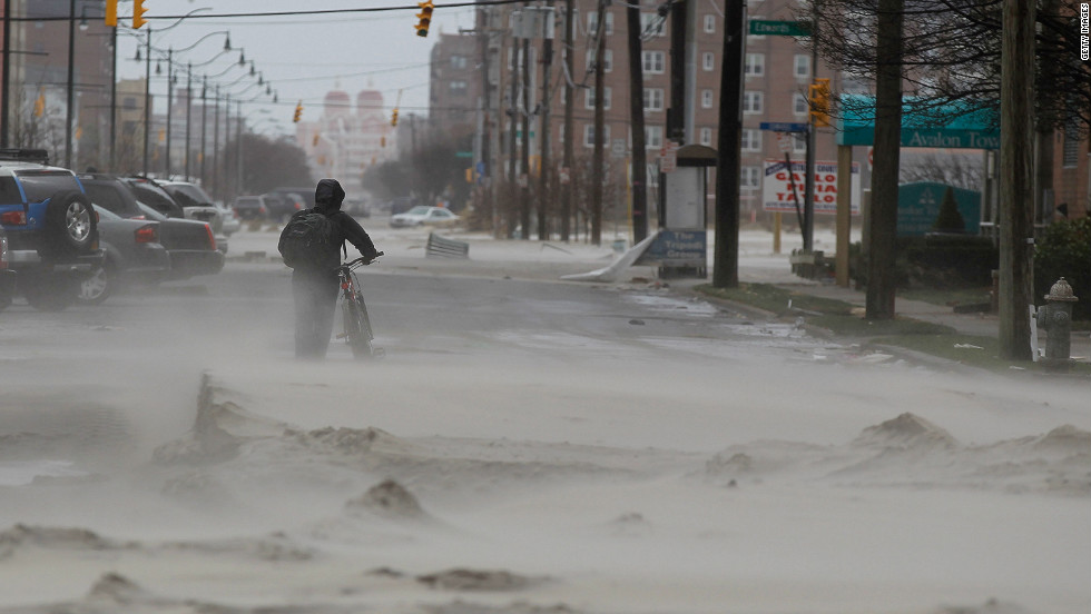 A resident walks down a street covered in beach sand due to flooding from Hurricane Sandy in Long Beach, New York on Tuesday.