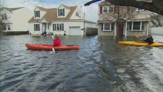 People kayak through streets to get home