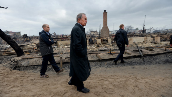 New York City Mayor Michael Bloomberg, center, views the damage Tuesday in the Breezy Point neighborhood of Queens, where a fire broke out during Superstorm Sandy and destroyed at least 80 homes.