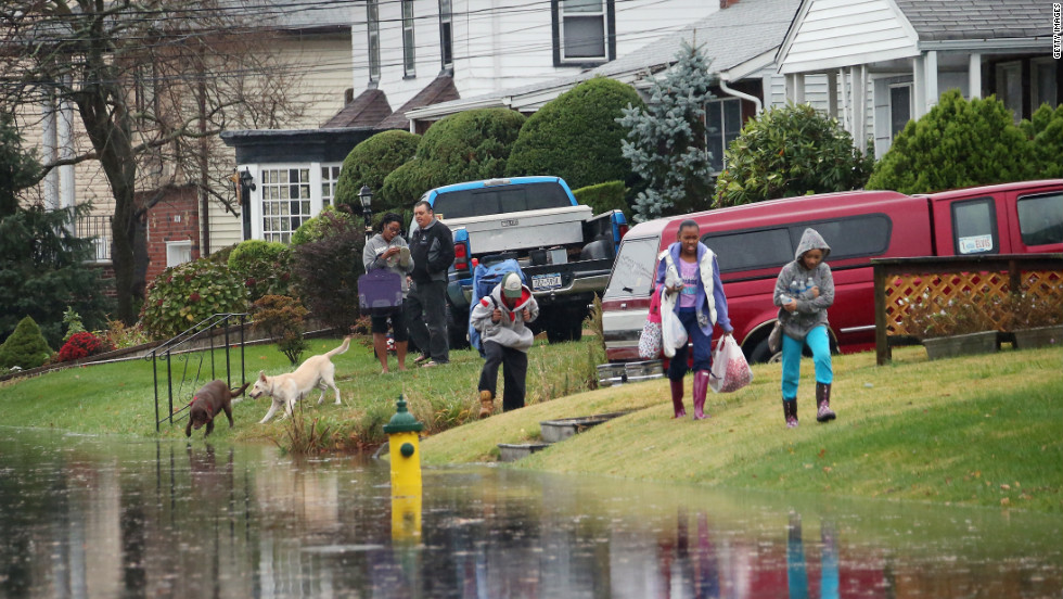 Kira Brizill leads family members as high tide and winds flood the street on Monday in Freeport, New York.