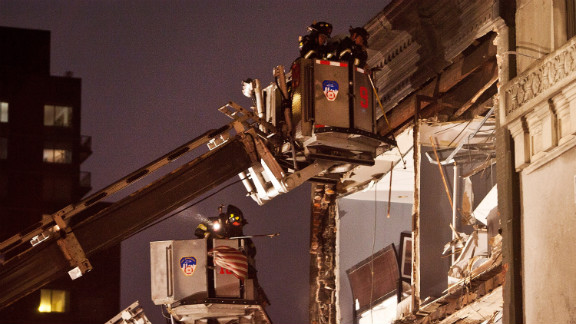 Firefighters evaluate an apartment building in New York City where the front wall collapsed due to Hurricane Sandy on Monday.