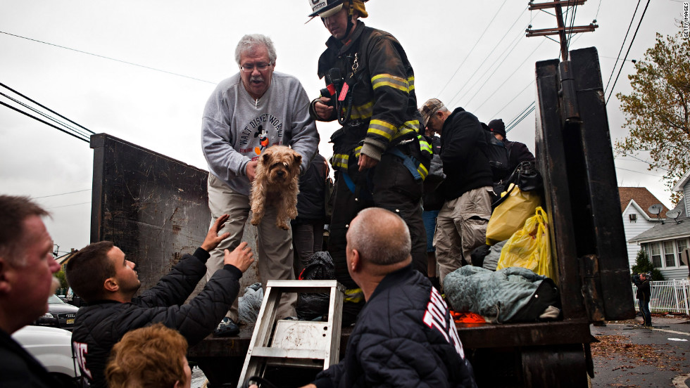 A man being evacuated in New York City hands a dog to first responders in flood waters caused by Hurricane Sandy on October 30, 2012.