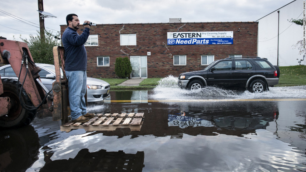 A man rides on the front of a forklift while recording flood damage for insurance purposes in Little Ferry, New Jersey, on Wednesday.