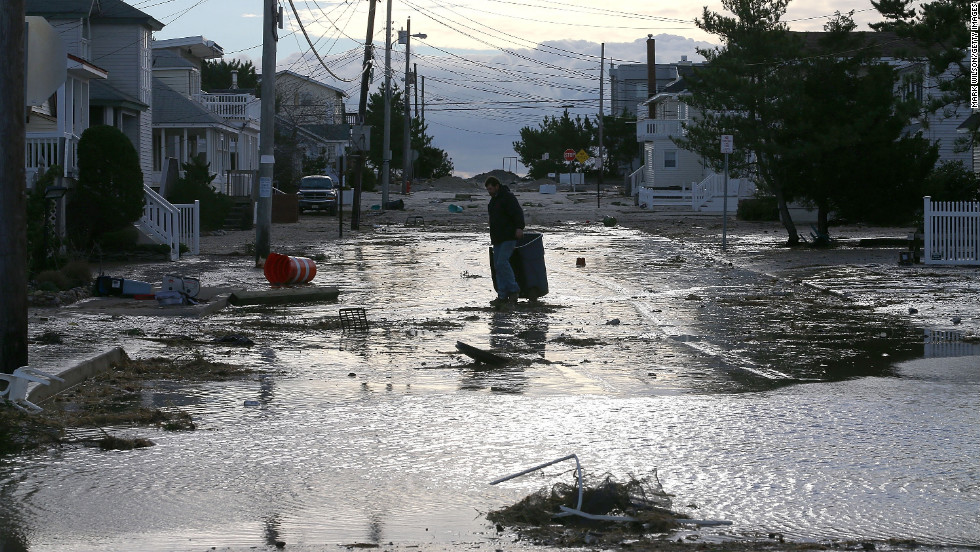 A man makes his way through floodwater and debris in Long Beach Island, New Jersey, on Wednesday.