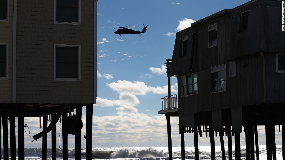 A helicopter flies past damaged homes in Long Beach Island, New Jersey, on Wednesday, October 31.