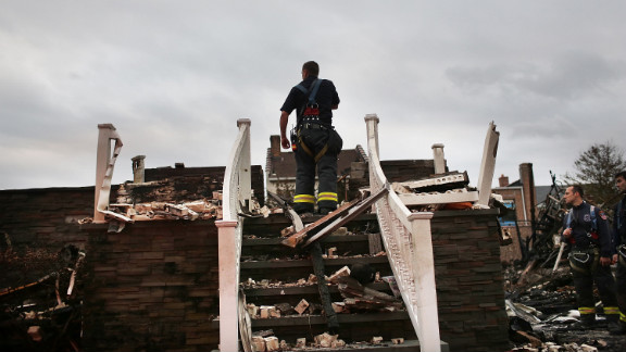 A firefighter stands on the porch of a home destroyed by fire in Queens on Wednesday.