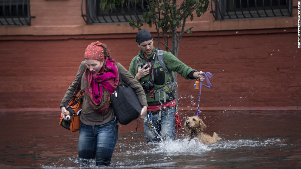 Blaine Badick and her fiancee Andrew Grapsas cross a flooded street with their dog while leaving their home in Hoboken.