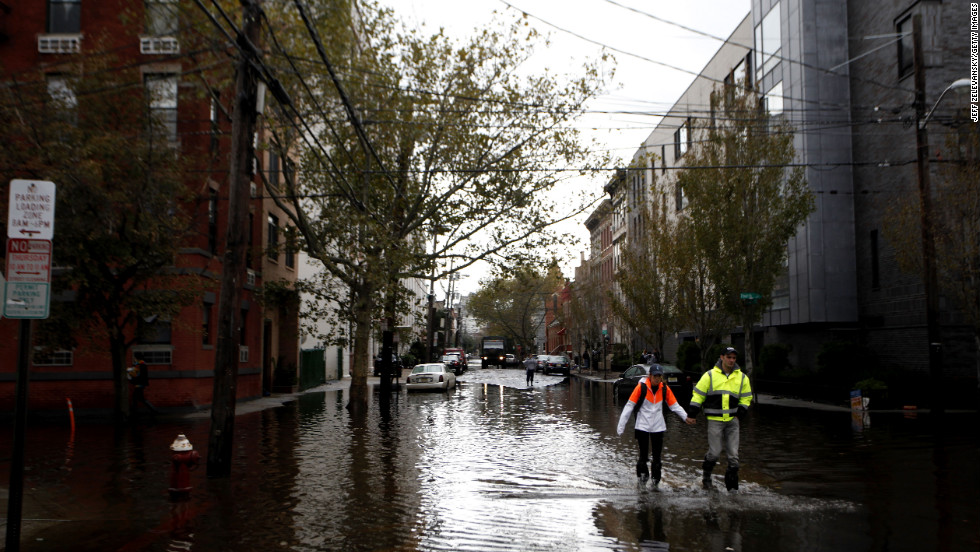 Residents traverse flooded streets as clean up operations begin in Hoboken, New Jersey.