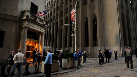 Traders stand outside of the New York Stock Exchange in New York on Wednesday. Stocks advanced as U.S. equity markets resumed trading for the first time this week after the storm.