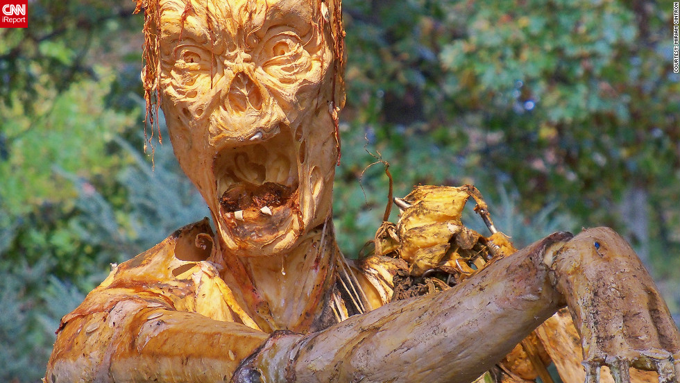"Ray Villafane's giant pumpkin creations are featured in New York Botanical Garden's special Halloween exhibition. Miriam Cintron, who captured this photo, said a lot of families with kids visited the garden - with the little ones not fazed one bit by the horribly scary and realistic zombie. ""It really looks like it's going to attack at any moment,"" she said. See all her <a href=""http://ireport.cnn.com/docs/DOC-865301"" target=""_blank"">macabre photos in her iReport.</a>"