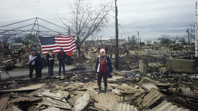 QUEENS, NY OCTOBER 31, 2012 Local residents return to widespread damage and fire that destroyed many houses, caused by Hurricane Sandy in the Breezy Point section of the Rockaways in Queens. They raised an American flag on the ruins of their home. Photograph by ALAN CHIN