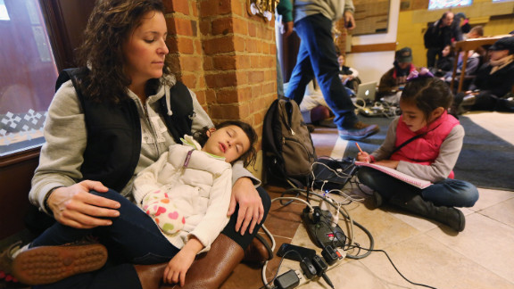 Bridget De La Torre holds her daughter Neve, 3, as daughter Paz sits nearby while they rest and charge devices on Thursday. They were at a shelter for those affected by Superstorm Sandy at Saints Peter and Paul Church in Hoboken, New Jersey. Bridget