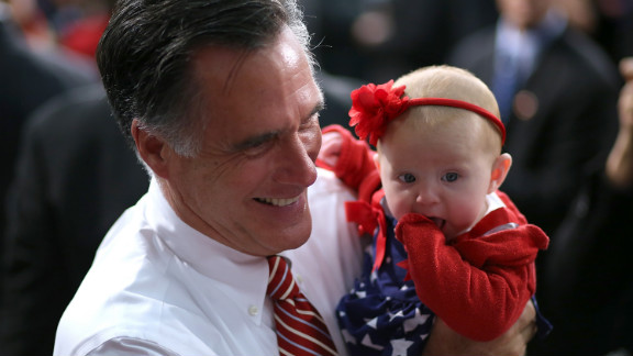 Mitt Romney holds a baby during a campaign event at Meadow Event Park on Thursday.
