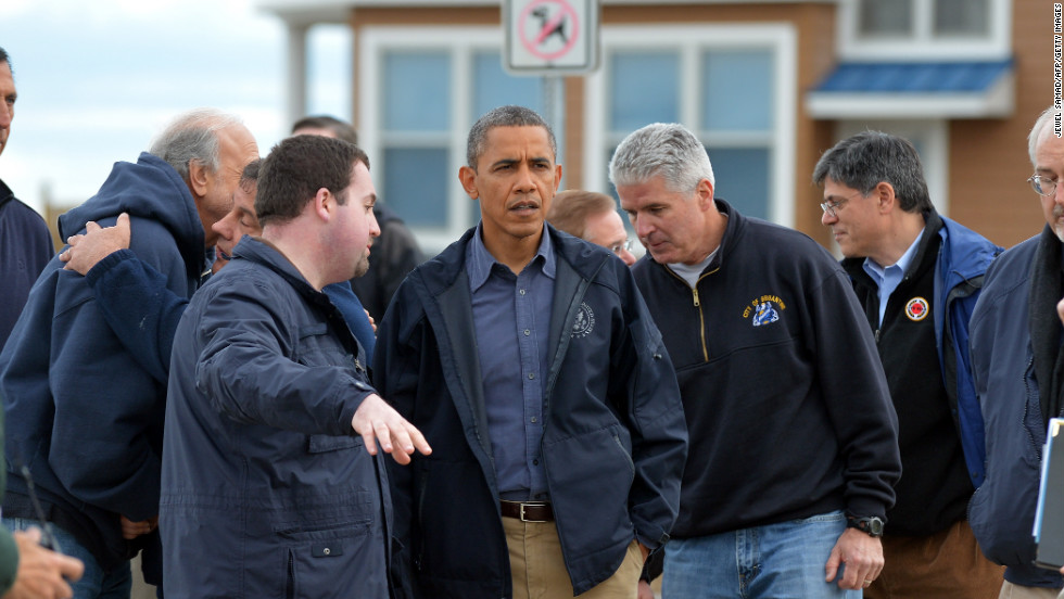 President Obama listens to local officials as they tour damaged areas.
