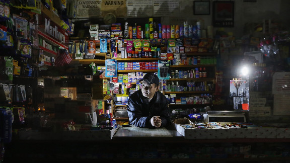 Park Choul works by flashlight in his deli in New York