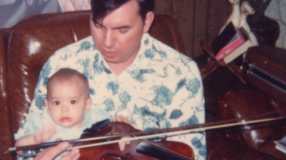 A baby Christal sits on Delmer's lap. He found solace in his music and would sometimes play the guitar eight hours a day.