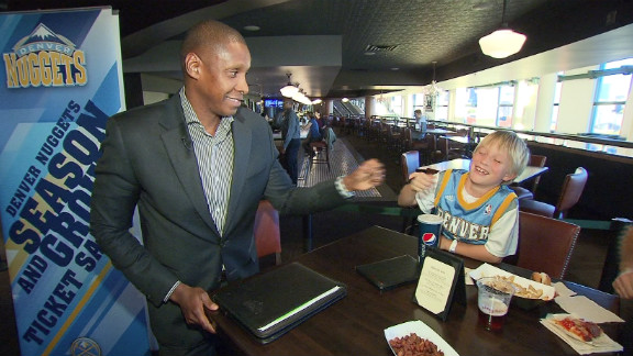 Ujiri bumps fists with a young Nuggets fan in Denver.