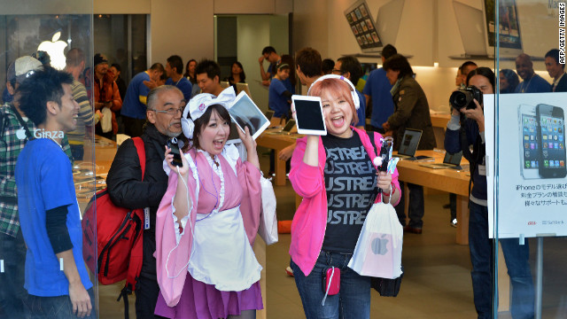 Customers show their newly purchased iPad Mini tablets at an Apple store in Tokyo on Friday.