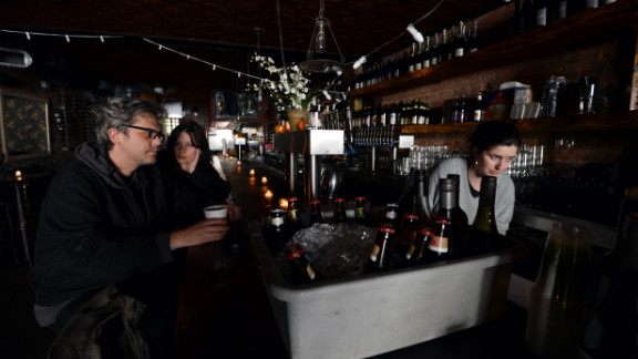 Matthew Mark Meyer, left, and Annie Barwick, center, sit in a darkened Randolf Beer Restaurant which is using generator power to reopen on Friday in New York City.