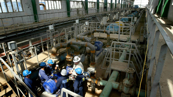 Iraqi workers fix a water pump at the Qarmat Ali water treatment facility in Basra, Iraq on Wednesday March 10, 2004.