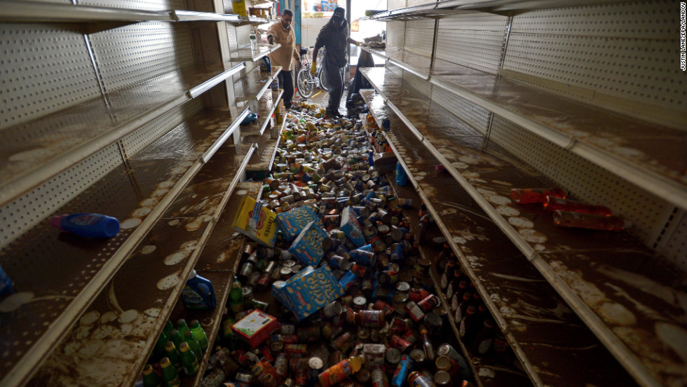 Men try to clean up the destruction in a flooded deli in Brooklyn, New York, on Friday.