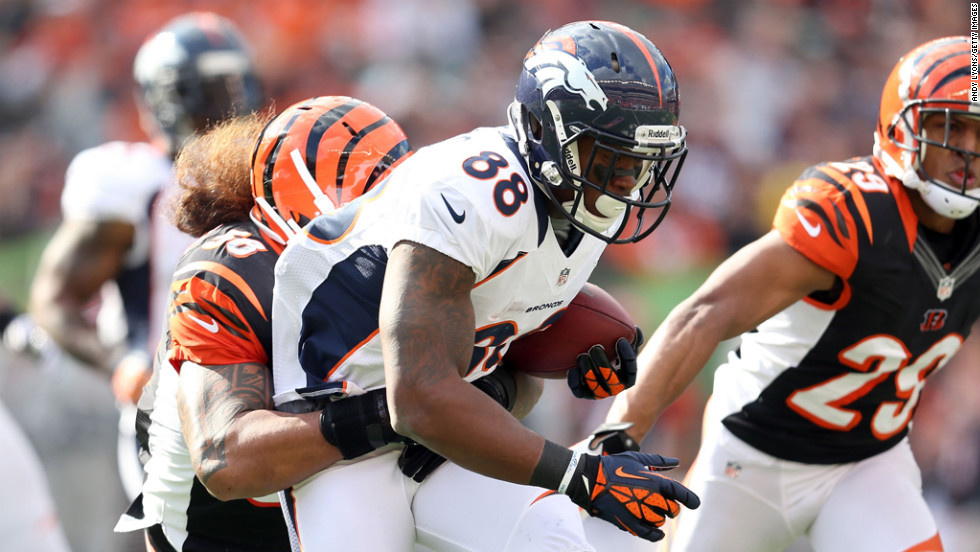 Demaryius Thomas of the Broncos runs with the ball while defended by Rey Maualuga of the Bengals.