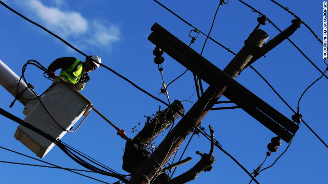In the aftermath of Superstorm Sandy, a work crew based in St. Louis, Missouri trims trees entangled in power lines on Broadway on November 3, 2012 in Bethpage, New York. With the death toll currently over 100 and millions of homes and businesses without power, the U.S. East Coast is attempting to recover from the effects of floods, fires and power outages brought on by Superstorm Sandy. New Jersey has begun rationing gas and the Department of Defense will be setting up mobile gas stations in New York City and Long Island. (Photo by Bruce Bennett/Getty Images)