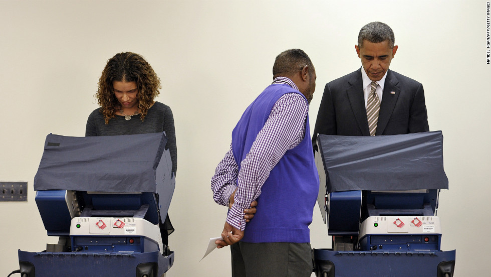 An election worker helps President Barack Obama as he votes early at the Martin Luther King Community Center in Chicago on October 25.