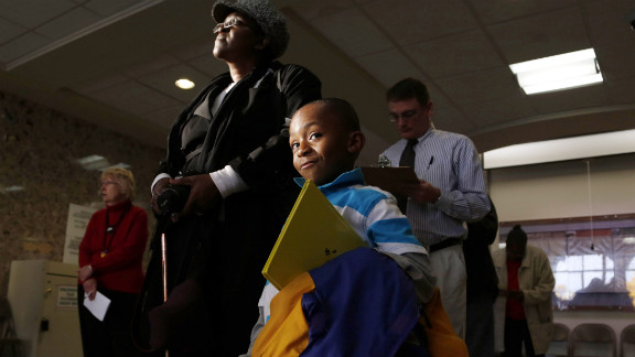 Jalani Hervey, 5, waits with his grandmother, Victoria Gross, while she stands in line to cast a ballot during early voting in Milwaukee on October 22.