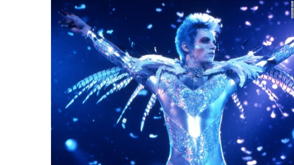 "In 1998's ""Velvet Goldmine,"" Christian Bale plays Arthur Stuartwan, a journalist investigating the disappearance of former rock star Brian Slade, played by Jonathan Rhys Meyers. Ewan McGregor also stars as Slade's one-time lover, Curt Wild."