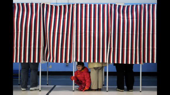 A young girl peered out from under a voting booth as her mother cast a ballot at the Bishop Leo O