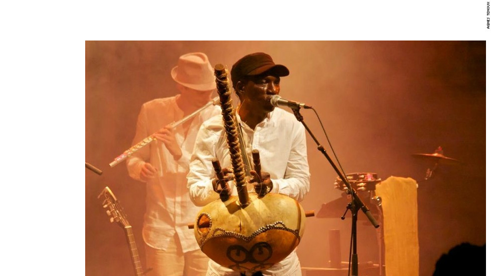 Guinean musician Djeli Moussa Conde, based in Paris for 20 years, plays a kora, an instrument similar to a harp.