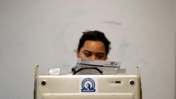 A voter takes a moment to read a paper ballot before casting her vote on Chicago
