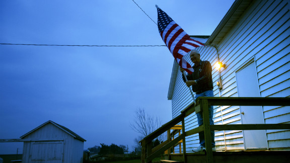 Election inspector Jim Nodorft prepared to hang the U.S. flag outside the Smelser Town Hall as polls opened at 7 a.m. in Georgetown, Wisconsin.