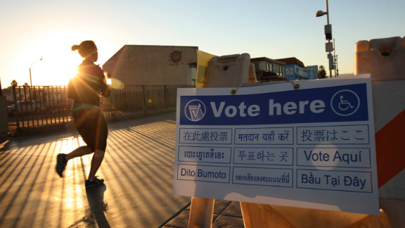 A jogger on The Strand in the Los Angeles area community of Hermosa Beach passed a directional sign to a polling place at sunrise.