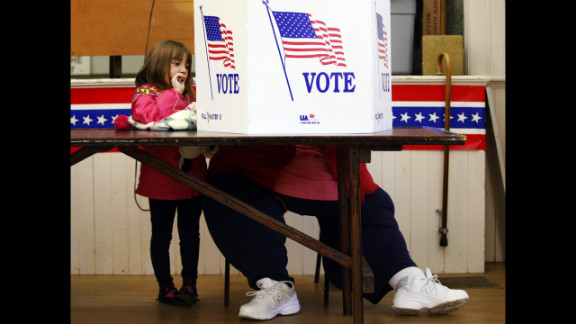 Kaira Ray watches as her grandmother Theresa Bigl votes at the old Town Hall in Bristol, New Hampshire.