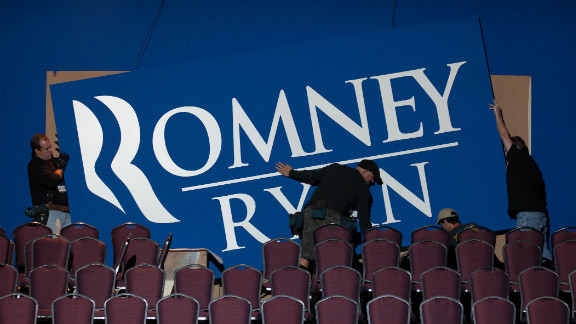 Workers put up signs Monday for Romney