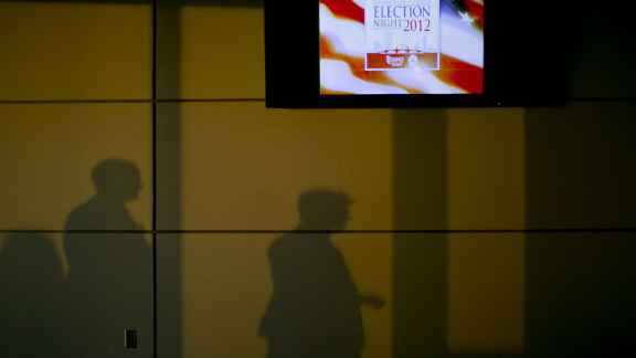 "Shadows were cast on a wall next to a television advertising ""Election Night 2012"" inside the Boston Convention & Exhibition Center, where Republican presidential candidate Mitt Romney was scheduled to speak Tuesday evening."