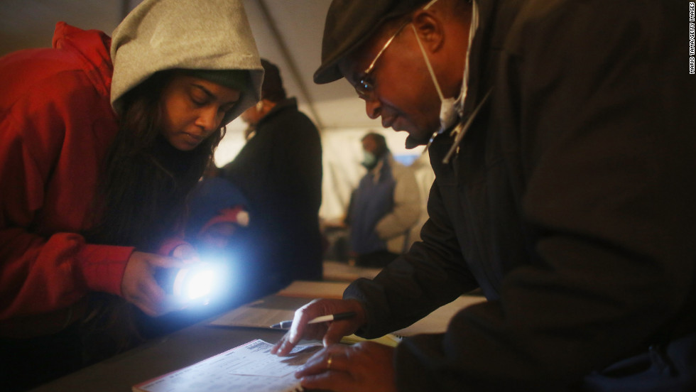 Voter Sheresa Walker used a flashlight for poll worker Lloyd Edwards in a tent set up as a polling place in Queens, New York. The area is still reeling from Superstorm Sandy.