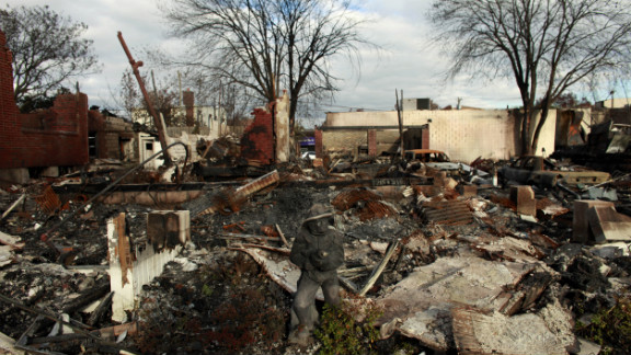 A statue of a firefighter stands in front of a burned down house Sunday in Rockaway, New York.