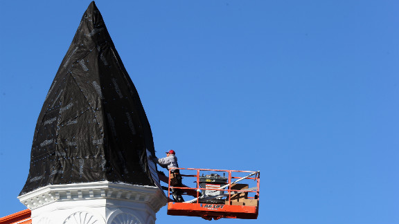 A workman repairs damage to the steeple of the First United Methodist Church on Sunday in Port Jefferson, New York.