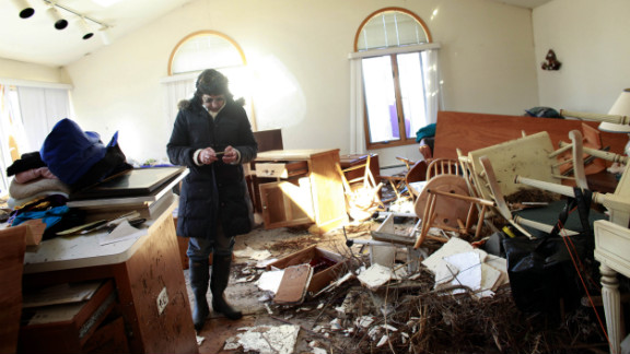 A woman sifts through her mother's damaged home for items to save Sunday in the Breezy Point neighborhood of Queens, New York.