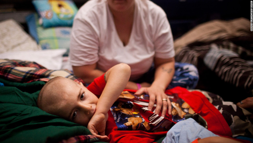 "Michael Fischkelta, 8, lies on his cot with his mother, Jenifer Wilson, in a Red Cross evacuation shelter set up in the gymnasium of Toms River High School on Monday, November 5, in Toms River, New Jersey. <a href=""http://www.cnn.com/2012/10/30/us/gallery/ny-sandy/index.html "">View photos of the recovery efforts in New York.</a>"