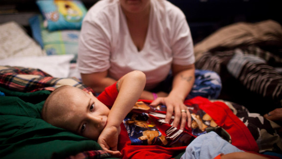 """Michael Fischkelta, 8, lies on his cot with his mother, Jenifer Wilson, in a Red Cross evacuation shelter set up in the gymnasium of Toms River High School on Monday, November 5, in Toms River, New Jersey. <a href=""""http://www.cnn.com/2012/10/30/us/gallery/ny-sandy/index.html"""">View photos of the recovery efforts in New York.</a>"""