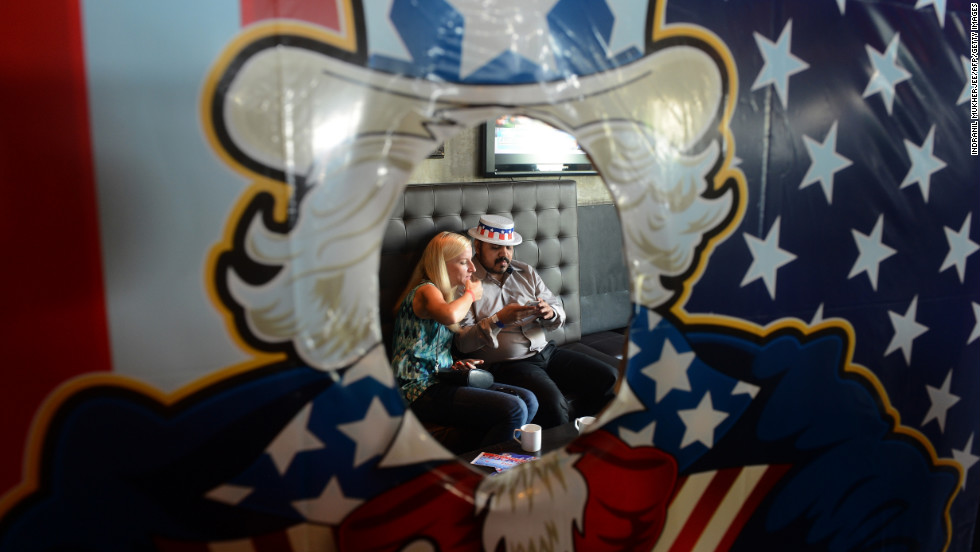 U.S. citizens check their mobile phones during an elections return party Wednesday in Mumbai, India.