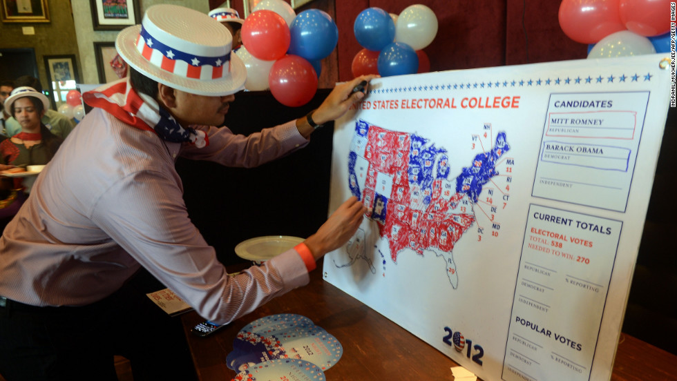 A U.S. consulate staff member marks a U.S. map in Republican and Democrat colors as the results of the U.S. presidential election are announced during a election returns party in Mumbai on Wednesday.