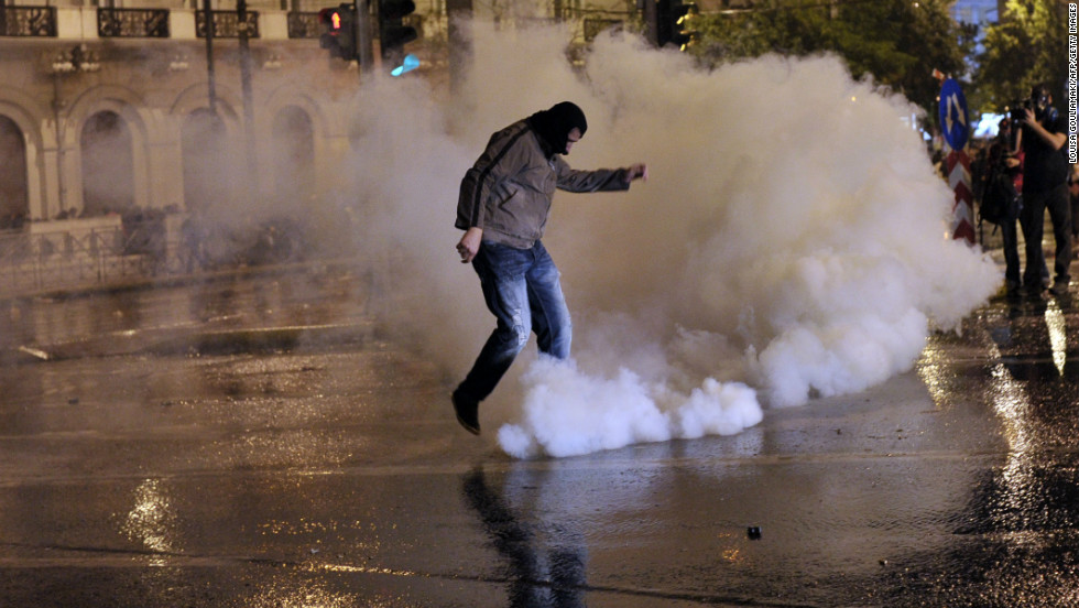 A protester kicks away a tear gas canister during a demonstration in Athens on November 7, 2012.