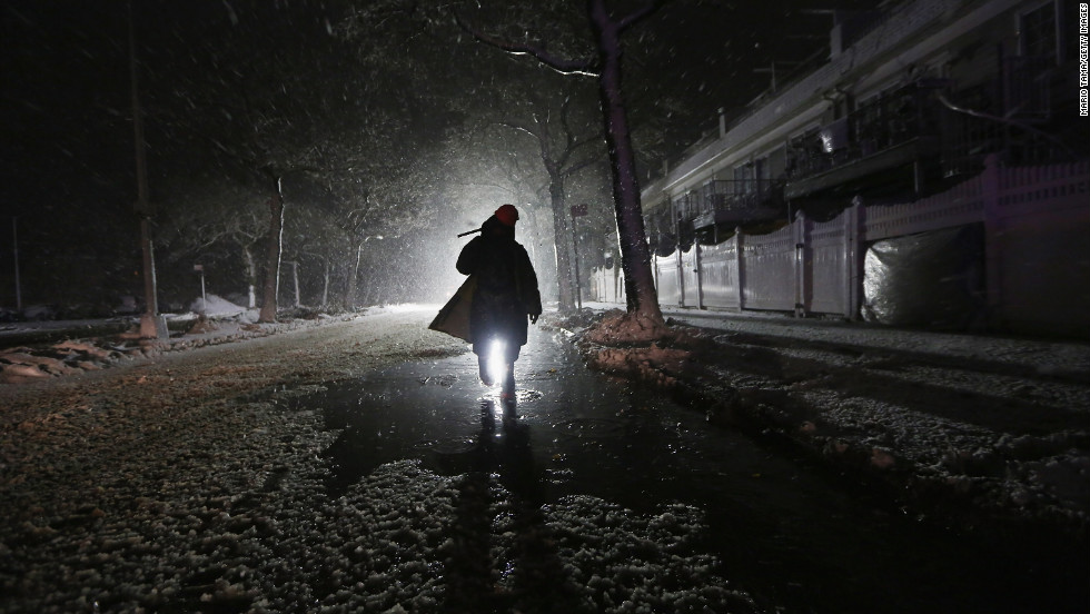 A repair worker is silhouetted by a police spotlight as he walks down a darkened street during a nor'easter on Wednesday in Rockaway.