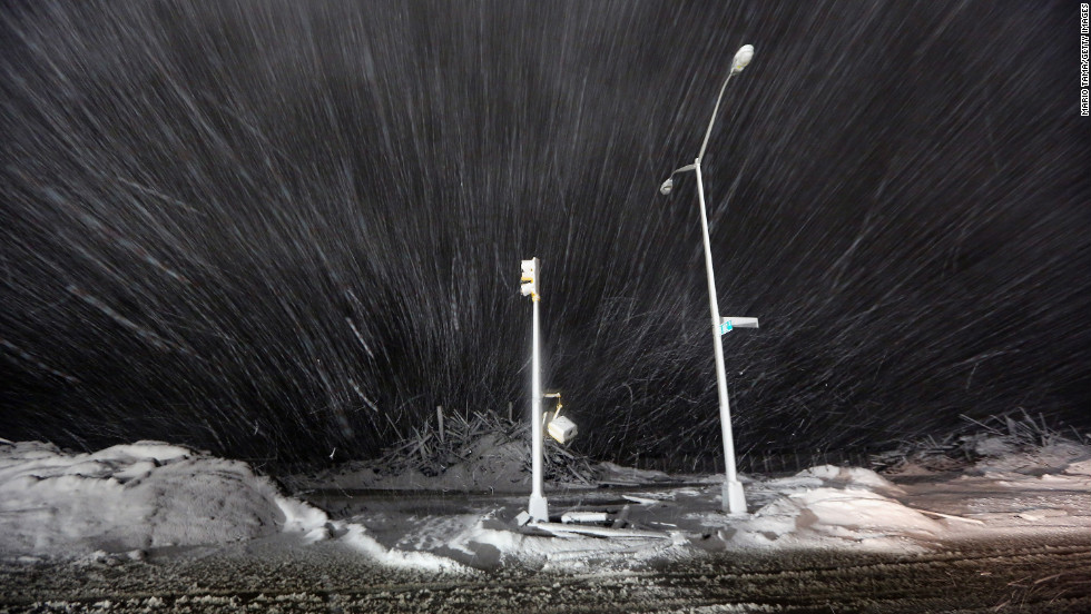 Snow blows past debris and nonfunctioning streetlights on Wednesday in Rockaway.